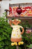 Ceramic figurine in garden with wooden bench on veranda in background