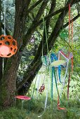 Wire chair hung from tree with colourful ribbons