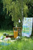 Picnic blanket, cushions, shelving holding water melons and logs and colourful cloth hung as a windbreak