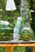 Watermelons with plastic cups and cutlery on a garden table