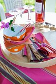 Spotty bowls, colourful fabric place mats and striped cutlery on wooden tray in garden