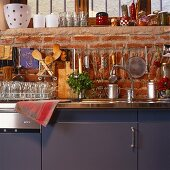 Detail of kitchen counter with blue doors against a brick wall