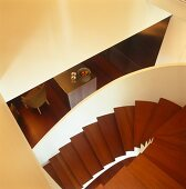 View down mahogany spiral staircase with solid, white balustrade