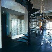 Open-plan interior with metal spiral staircase in front of glass brick wall and fitted cupboards with mirrored doors
