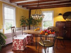 Dining area with various chairs in yellow-painted country house dining room