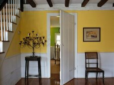 Foyer of rustic country house with yellow-painted walls and open door