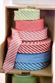 Rolls of fabric trim in wooden shelf compartment