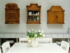 Bouquet on white dining table in front of various wooden wall cabinets