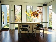 Designer metal chairs at table in front of floor-to-ceiling windows with view of garden