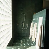 Contemporary bathroom with grey tiles on walls and floor and pattern of light on wall