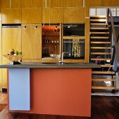 Kitchen counter with colourful front panel in open-plan kitchen