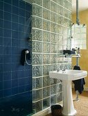 Retro pedestal washstand against glass brick wall next to blue-tiled wall
