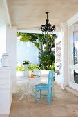 Blue-painted chair and bistro table on neo-classical veranda of Mediterranean villa