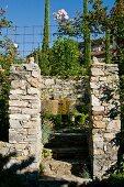 Blick zwischen Natursteinpfosten in mediterranen Garten