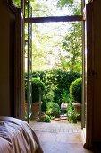 Blick vom Schlafzimmer durch offene Terrassentür auf sonnenbeschienene Terrasse mit Buchsbaumkugeln in Töpfen