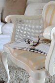 Relax with a book - white-painted chair with cushioned seat and curved frame