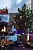 Christmas tree in ceramic pot in front of brick fireplace with Oriental tray table in foreground