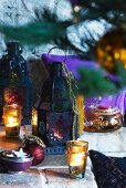 Oriental Christmas tabletop arrangement of lanterns and tealight holders of coloured glass