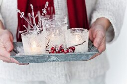 Hands holding tray of lit tealights in ornamented holders and holly berries