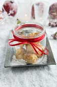 Jar of coconut macaroons on tray in artificial snow