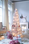 Christmas gift giving- artificial Christmas tree made from white feathers with lights and presents on flokati rug in traditional interior