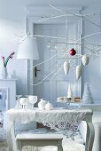 Christmas arrangement of twigs above side table with collection of white glass ornaments