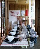 Festive table with linen table mats, plates, bowls and labelled planters as place cards