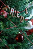Christmas tree decorated with red apples, woollen yarn and chocolate letters