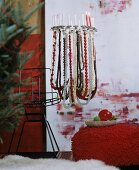 Festive chandelier made from lampshade frame decorated with strings of beads and candles