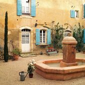 Fountain in courtyard of French country house with turquoise shutters on weathered facade