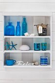 Blue bottles and glass in small, white, shabby-chic shelving unit