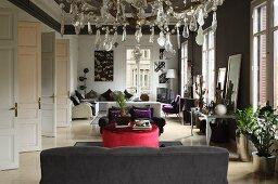 Elegant salon with sofa set, tall windows and double doors