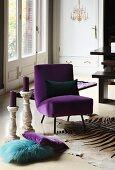 Chair with purple velvet upholstery on zebra-skin rug; scatter cushions and candlesticks on floor