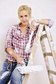 Renovierungsarbeiten - Frau auf der Leiter sitzend mit Pinsel und Farbrolle in der Hand