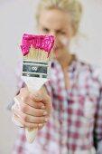 Renovierungsarbeiten - Frau hält einen in Farbe eingetauchten Pinsel in der Hand