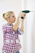 Renovierungsarbeiten - Frau bohrt Loch in die Wand