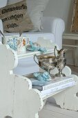 Silver goblets and cups on white wooden stepladder