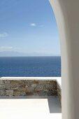 Blick durch Rundbogen über Terrasse mit Natursteinmauer auf das Meer