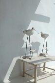 Moderne Tierfiguren mit Vogelmotiv auf rustikalem Holzhocker