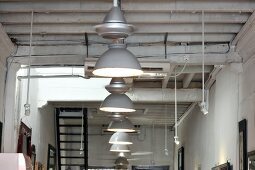 Row of pendant lamps with metal lampshades hanging from simple wooden ceiling in restaurant interior