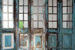 Peeling paint on wooden wall with lattice windows and doors