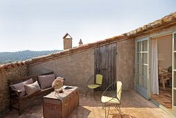Fifties-style wire armchairs and travelling trunk used as table on Mediterranean roof terrace