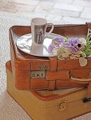 Mug with printed picture, plate and flowers on top of two old leather suitcases