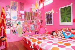 Mädchenzimmer mit rosa Wänden, zwei Betten, bunter Wanddekoration und Lichterkette