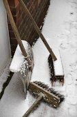 Two brooms and snow shovel at house wall