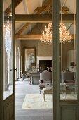 Umbau einer alten Mühle - Blick durch offene Tür in eleganten Wohnraum mit neubezogenen Rokoko Sesseln und Kronleuchter