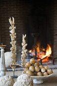Schale mit künstlichem Obst und Antiquitäten auf Tisch vor Kaminfeuer