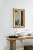 Rustikaler Waschtisch mit Waschschüssel auf Holzplatte und Designer Armatur vor Wand mit gerahmtem Spiegel