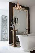 Freistehende Vintage Badewanne und mehrarmiger Kerzenständer auf antiker Stele vor raumhohem Wandspiegel am Raumteiler und moderner Schubladenschrank aus Metall