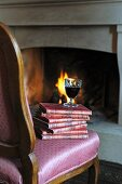 Glass of red wine on stack of books by the fireplace